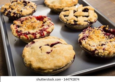 Six homemade fresh fruit pies on a tray made with strawberries raspberries blueberries blackberries