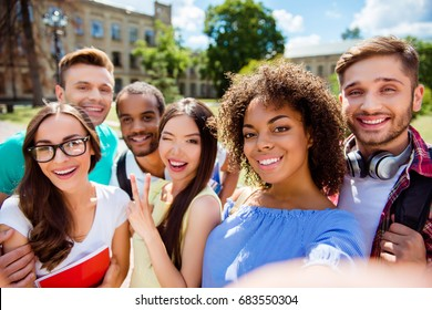 Six international students with beaming smiles are posing for selfie shot, african attractive lady is taking, outside school building. Gathered, cheerful, smart and successful youth