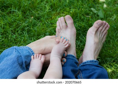 Six legs feet in grass, father's dad's mum's mother's boy's baby's, family concept
