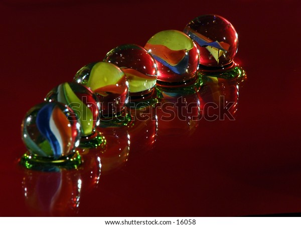 Six lined up marbles floating on a red shiny reflecting surface.
