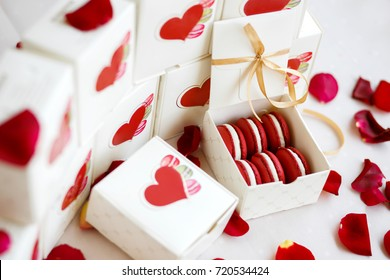Six marsala burgundy dark red macarons in a stylish decorated gift box for Valentine's day, New Year or other holiday or anniversary on a table with rose petals