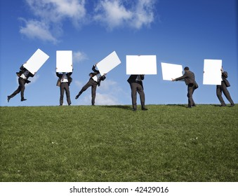 Six men on the crest of a grassy hill, carrying blank white signs or boards.