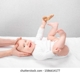Six month baby girl receiving osteopathic or chiropractic treatment in pediatric clinic. Manual therapist manipulates child's head and neck
