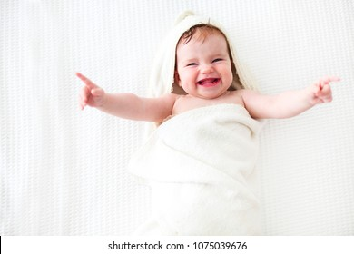 Six month baby wearing towel after bath. Childhood and baby care concept