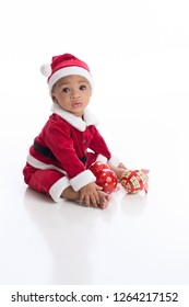 Six Month old baby girl wearing a Santa Claus costume. She is sitting on a white, seamless background with Christmas ornaments.