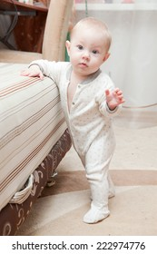 Six month old baby standing next to the bed in the room.