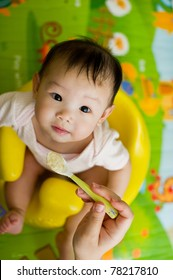 Six month old South East Asian Chinese baby girl sitting in a yellow seat, being spoon fed