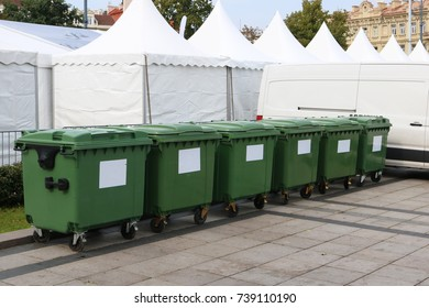 Six new plastic green garbage standard containers. Back side of the city sports festival. In the background - trading canvas tents