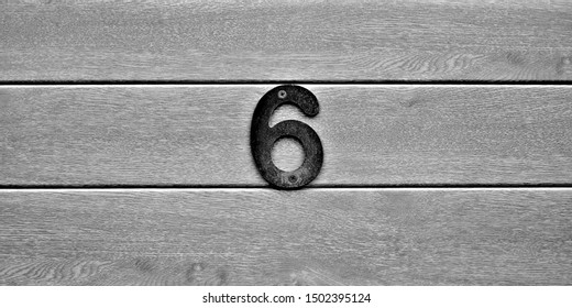 Six, number 6 on vertical wooden planks.