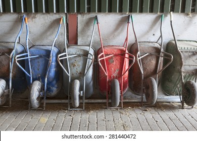 six old and rusty wheelbarrows rest against wall of farm barn
