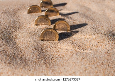 six of one Euro coins stand on edge in the sand