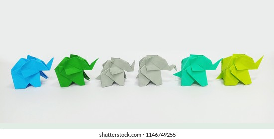 Six origami elephants are walking in line, isolated on white.