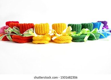 Six Pairs Of Hand Knitted Rainbow Colored Baby Booties With Colorful Ribbons On A White Background - Empty Space For Text, Information Or Promotion