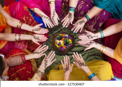 Six pairs of henna decorated female hands arranged in a circle on a colorful background.