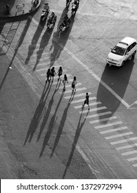 Six people crossing on crosswalks is white line at Ho Chi Minh city, Vietnam on day, long shadow on road surface make impression scene from high view, group of people so very tiny