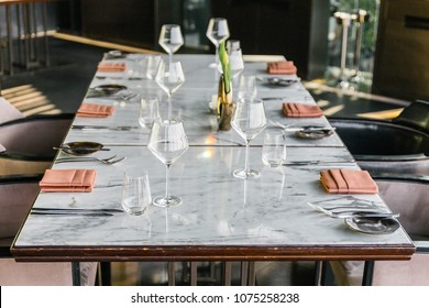 Six people dinner table with plates, knives, forks, wine glasses, glasses and napkins on marble table top.