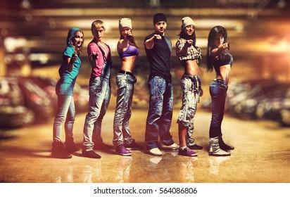 Six people modern dancers team. Showing pointing hand sign. Underground car parking interior.
