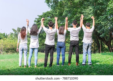 Six people standing and holding hands in the park forest at outdoors with green tree background. concept of teamwork, spirit, meeting; seminar; activity and community.