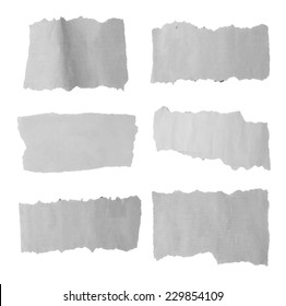 Six pieces of torn paper on plain background