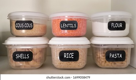 Six plastic containers with dry food (couscous, red lentils, white flour, pasta shells, rice, elbow pasta) in the kitchen cupboard.