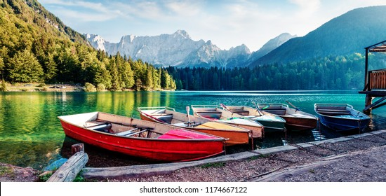 Six pleasure boats on Fusine lake. Panoramic evening scene of Julian Alps with Mangart peak on background, Province of Udine, Italy, Europe. Traveling concept background.