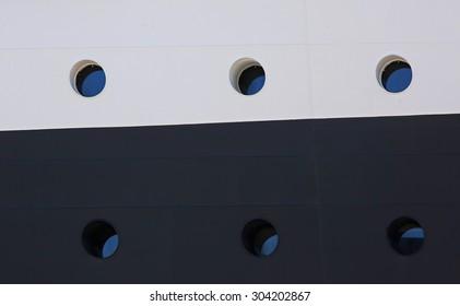 Six portholes on a multi-colored side of a cruise ship.