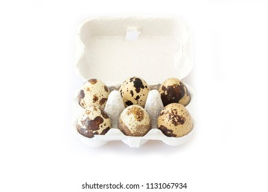 Six quail eggs in a box on white background