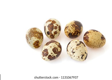 Six quail eggs on white background