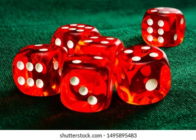 Six red acrylic transparent dices for games. Gambling translucent dices on dark-green velvet surface, close-up high resolution.