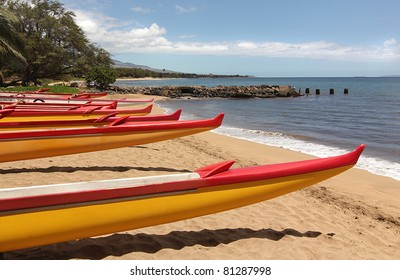 Six red and yellow ocean kayaks on the beach sand at the edge of the Pacific Ocean in Maui, Hawaii.