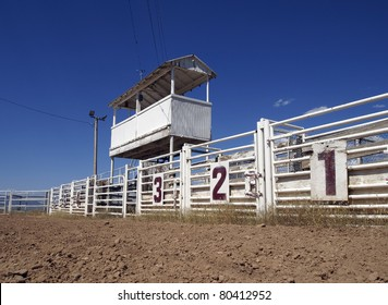 Six rodeo gates beneath the announcer's booth at a rural rodeo.