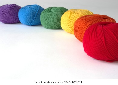 Six Skeins In Rainbow Colors: From Purple to Blue, Green, Yellow, Orange, And Red