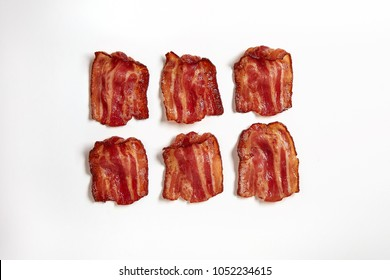 Six slices of fresh fried bacon lined up in a row, isolated on a white background
