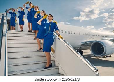 Six slim beautiful stewardesses saluting on the aircraft steps
