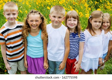 Six smiling children stand together on lawn full of yellow flowers, high angle view