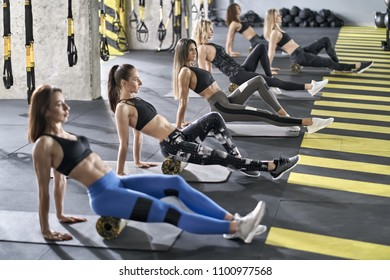 Six sportive girls are training with black-yellow foam rollers on the gray mats in the gym. They are wearing the multicolored sportswear: pants, tops and sneakers. Women are looking forward.