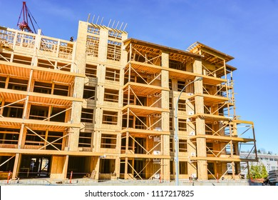 Six storey frame building under construction on concrete foundation bed on blue sky background