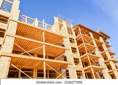 Six storey frame building under construction on blue sky background