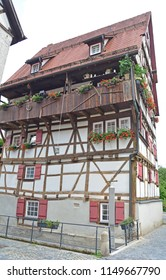 Six storied half-timbered house in the German Swabian Jura region. Built next to a canal. A suspended watering can provides the water for the window boxes