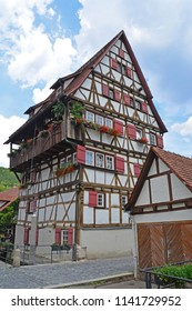 Six story half timbered traditional  house in the German Swabian Jura region. Built next to a canal. A suspended watering can provides the water for the window boxes
