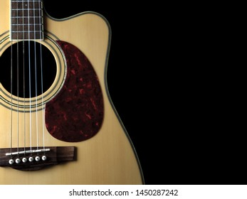 six - string acoustic guitar  on a black background. low key. music day