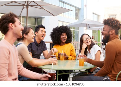Six trendy millennial friends sit drinking cold brews talking and laughing outside a cafe