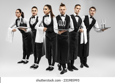 Six waiters with glasses and towels