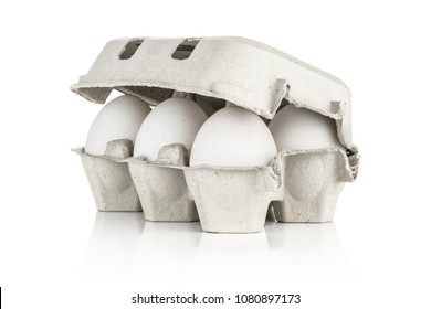 Six white chicken eggs in a paper grey crate isolated on white background