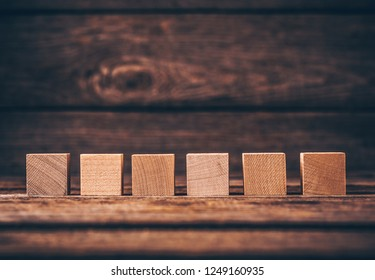 Six Wooden Cubes on Wood Background with Copyspace