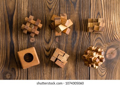 Six wooden puzzles of differing complexities arranged in two rows on a wood background with decorative woodgrain