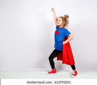 Six year blonde girl dressed like superhero having fun at home. White wall on background