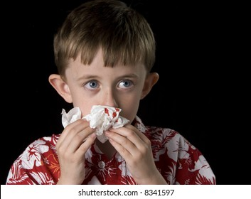 Six year old boy with a bloody nose. Horizontal framing on a black background.