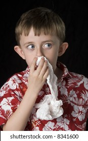 Six year old boy looks concerned about his bloody nose. Vertical framing against a black background.