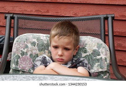 A six year old boy sulking, arms folded, slumped in his chair.